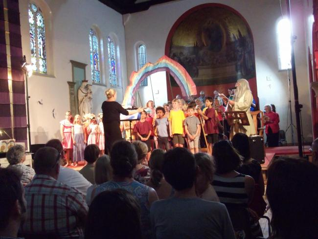 SINGING SENSATION: The final rainbow chorus, plus a representation of God, by the combined singers.