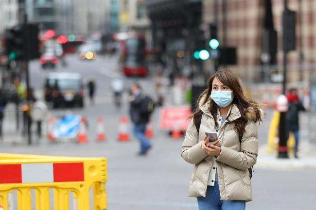 Precaution - a woman wearing face a mask near Bank, London, yesterday as the coronavirus infection spread Picture: Aaron Chown/PA Wire