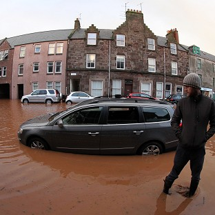 A man views his flooded car on the high street in Stonehaven, near Aberdeen