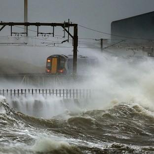 Harwich and Manningtree Standard: A train is lashed by waves along the coast at Saltcoats as Scotland has been warned to expect a storm surge.
