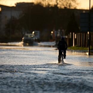 Harwich and Manningtree Standard: A man cycles down a flooded road in Chertsey, Surrey