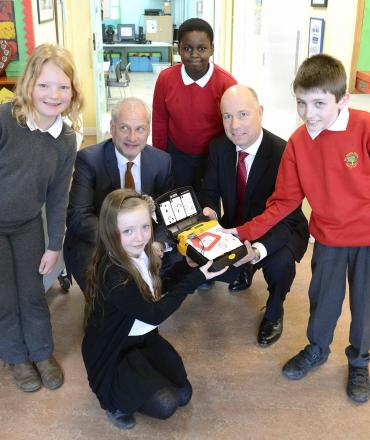Firm presents defibrillator to school