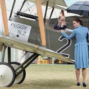 The Duchess of Cambridge looks on as the Duke of Cambridge climbs into the cockpit of a Sopwith Pup as they visit the Omaka Aviation Heritage Centre in Blenheim, during their official tour to New Zealand