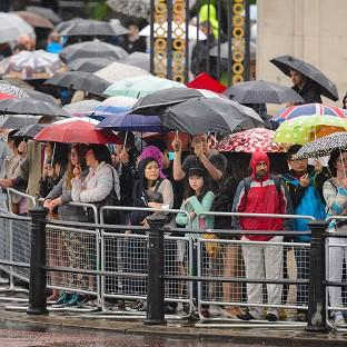 Spectators sheltering from heavy rain as they watched the final rehearsal of Trooping the Colour
