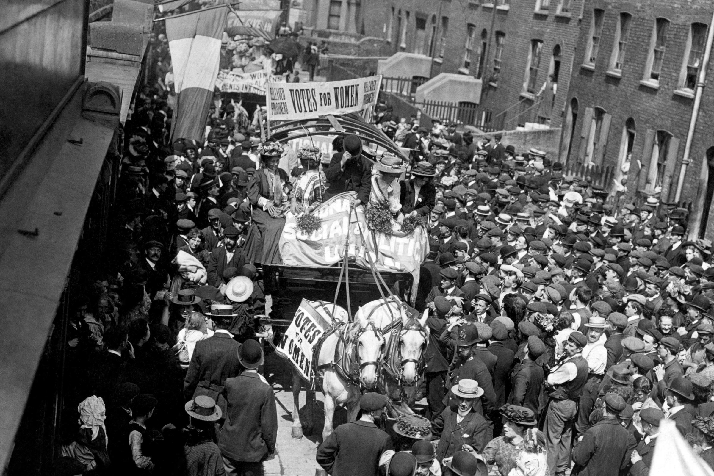 Crowds line the streets as they watch suffragettes pass by following their release from Holloway Prison (PA)