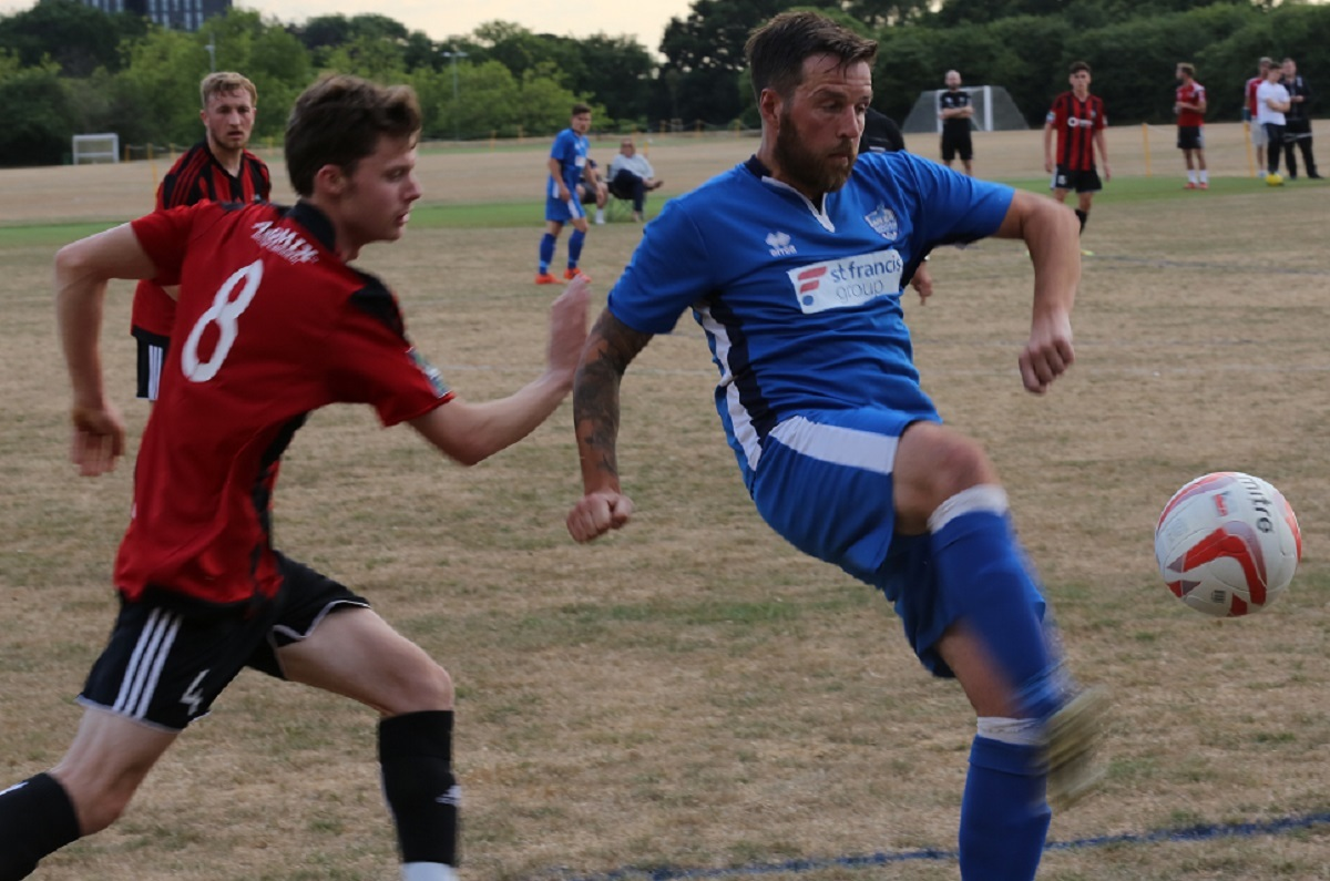 Louie Newland (blue kit) in pre-season friendly action for Brantham Athletic against former side Brightlingsea Regent Picture: Gavin Aplin