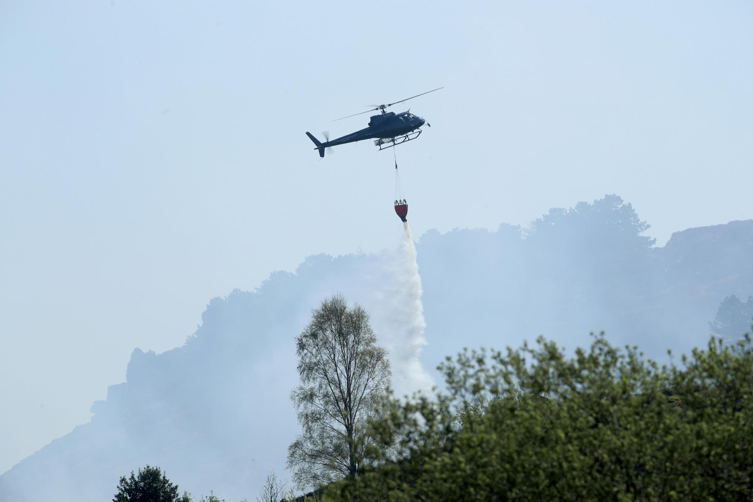 Firefighters use a helicopter to drop water as they tackle a large fire on Ilkley Moor